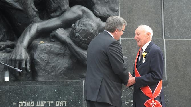 Polish President Bronislaw Komorowski , left, decorates Simha Rotem, one of the last living Warsaw Ghetto insurgents,  with the Grand Cross of the Order of the Rebirth of Poland in front of the Warsaw Ghetto Uprising memorial, during the revolt anniversary ceremonies in Warsaw, Poland, Friday, April 19, 2013. Sirens wailed and church bells tolled in Warsaw as largely Roman Catholic Poland paid homage Friday to the Jewish fighters who rose up 70 years ago against German Nazi forces in the Warsaw ghetto uprising. (AP Photo/Alik Keplicz)