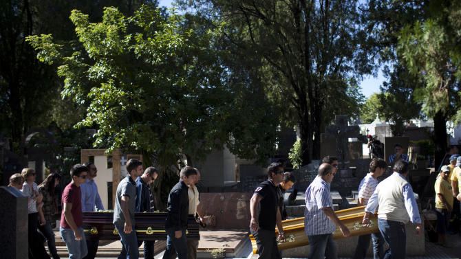 Relatives and friends carry the coffins of two brothers, Pedro and Marcelo Salla, who died in a nightclub fire, through a cemetery as they prepare to bury them in Santa Maria, Brazil, Monday, Jan. 28, 2013.  A fast-moving fire roared through the crowded, windowless Kiss nightclub in this southern Brazilian city early Sunday, killing 233 people. Many of the victims were under 20 years old, including some minors. (AP Photo/Felipe Dana)