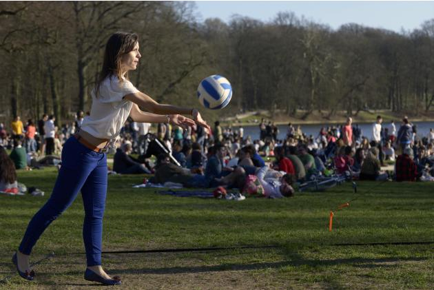A girl plays volleyball in a park on a warm day in Brussels
