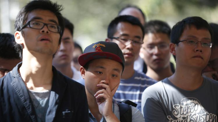 USC students and faculty cry as they watch a memorial service for murdered USC graduate student Ji Xinran on a television screen on the USC campus in Los Angeles