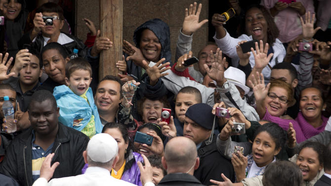 People greet and take pictures of Pope Francis as he visits the Varginha slum in Rio de Janeiro, Brazil, Thursday, July 25, 2013. Francis on Thursday visited one of Rio de Janeiro's shantytowns, or favelas, a place that saw such rough violence in the past that it's known by locals as the Gaza Strip. (AP Photo/Victor R. Caivano)
