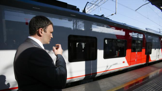 """In this photo taken Monday, Oct. 28, 2013 a security agent watches a commuter train with Russian President Vladimir Putin aboard, arriving at the newly built Adler railway station that serves as a hub for the link between the airport and the Alpine venues of the Winter Olympics at the Black Sea resort of Sochi, southern Russia. The organizers of the 2014 Winter Games in Sochi have introduced some of the most extensive identity checks and sweeping security measures ever to be seen at an international sports event, trying to fulfill their pledge to make the Winter Games in Sochi """"the safest Olympics in history."""" (AP Photo/Alexander Zemlianichenko)"""