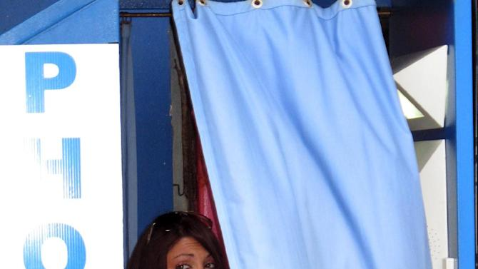 "This June 14, 2012 photo shows Deena Cortese, a cast member of MTV's ""Jersey Shore"" series, sitting in a photo booth smoking a cigarette while filming an episode of the show in Seaside Heights, N.J. Cortese has a municipal court date next month for a disorderly persons charge for allegedly dancing in the street and interfering with traffic. (AP Photo/Wayne Parry)"
