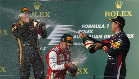 Lotus Formula One driver Raikkonen, Ferrari's Alonso and Red Bull's Vettel spray champagne as they celebrate after the Australian F1 Grand Prix in Melbourne