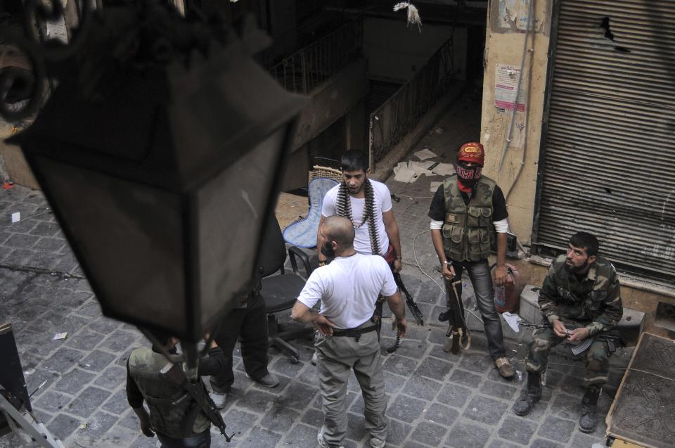 In this Tuesday, Nov. 6, 2012 photo, Syrian rebels gather in the Old City of Aleppo, Syria, a listed UNESCO World Heritage Site that was gutted in October and which is now controlled by the Free Syrian Army.(AP Photo/Monica Prieto)