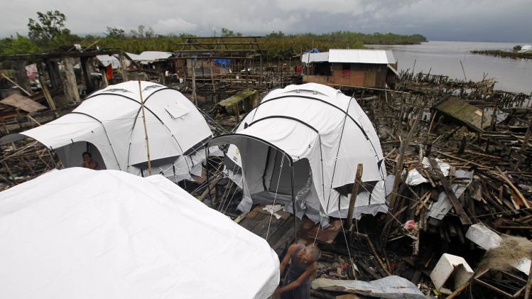 A typhoon survivor fixes his tent which serves as his temporary shelter after his house was devastated by super typhoon Haiyan a month ago at the battered town of Basey