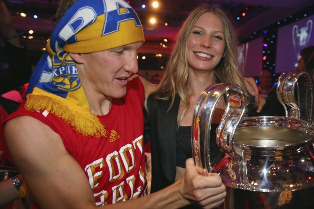 Bayern Munich's midfielder Bastian Schweinsteiger and his partner Sarah Brandner hold the Champions League trophy at the team's banquet in London