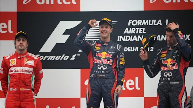 Sebastian Vettel of Germany (C) gestures at the podium with third-placed teammate Red Bull-Renault driver Mark Webber of Australia (R) and second-placed Ferrari driver Fernando Alonso of Spain (AFP)