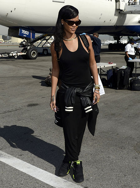 Rihanna upon boarding #RihannaPlane - Generally, public displays of sweatpants don't get my endorsement, but fitted, monochrome black ones styled with neon-detailed sneakers and lots of sparkly, subst