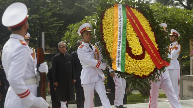 Vietnamese soldiers carry a wreath as India's President Pranab Mukherjee follows during a wreath-laying ceremony at the War Martyrs monument in Hanoi
