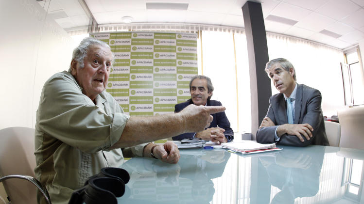 In this photo taken Oct 22, 2012,  Felix Valls, bearer of stock shares from Bankia, left, Ricard Torres, president of the  ApacBank association, which represents hundreds of Bankia clients who have had their money frozen, right, and Salvador Sastre, Apacbank spokesperson center, during a meeting in Valencia, Spain. Valls followed the bank manager's advice and invested his entire savings in the bank's stocks, he did it without thinking. It was a simple question of loyalty. After all, how could he doubt the local bank that opened an account for him just after he was born in 1935 with a gift of 5 pesetas, a small fortune in those days, as a sign of respect to his parents, who were life-long customers? Now the 77-year-old Valls feels betrayed as he finds himself locked out of touching his hard-earned money. (AP Photo/Alberto Saiz)