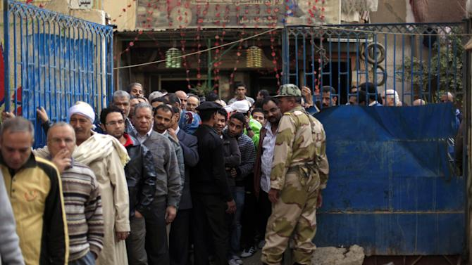 FILE - In this Saturday, Dec. 15, 2012 file photo, Egyptian men line up outside a polling station to cast their votes during a referendum on a disputed constitution drafted by Islamist supporters of President Morsi in Cairo, Egypt, Saturday, Dec. 15, 2012. Barely a third of voters turned out for the referendum on a constitution meant to be a historic milestone in setting Egypt's future. Perhaps it was fatigue after multiple elections, or a frustrated shrug. (AP Photo/Khalil Hamra, File)