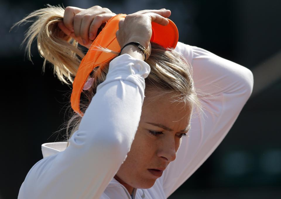 Russia's Maria Sharapova adjusts her cap during a training session for the 2013 French Open tennis tournament, at Roland Garros stadium in Paris, Saturday May, 25, 2013. (AP Photo/Christophe Ena)