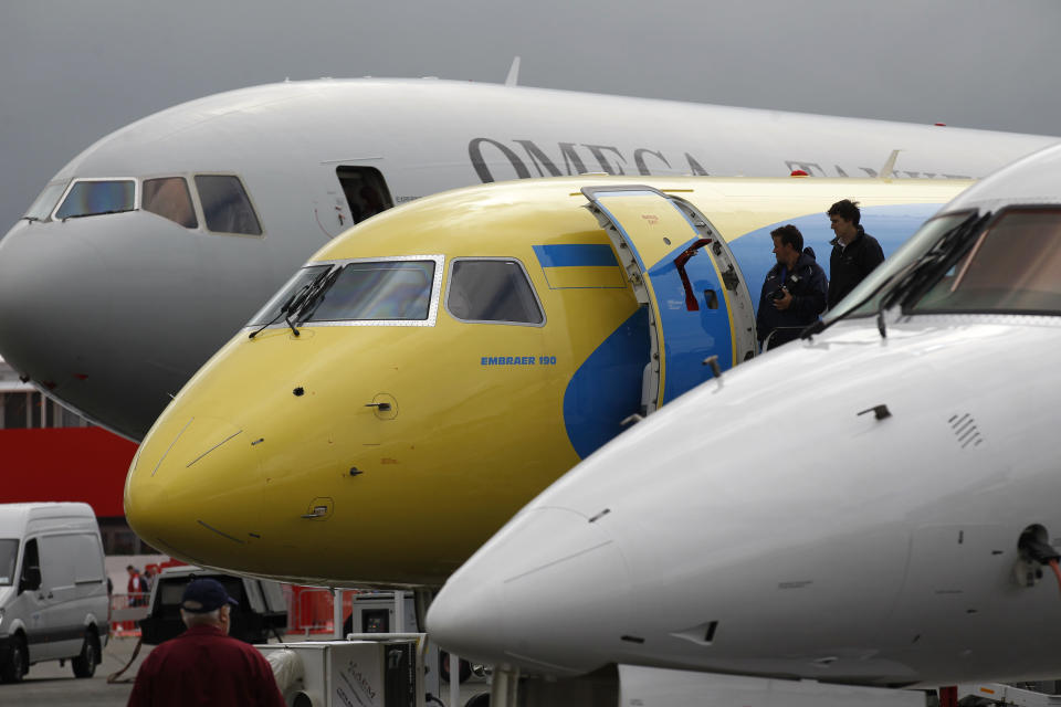Visitors look at an aircraft on display at the Farnborough International Airshow, Farnborough, England, Monday, July 9, 2012. (AP Photo/Sang Tan)