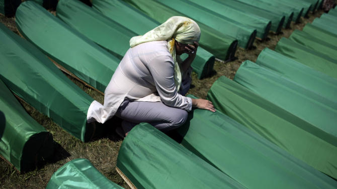 A woman mourns beside the coffin of her relative among the over six-hundred displayed at the Potocari memorial cemetery near Srebrenica, some 160 kilometers east of Sarajevo, Bosnia and Herzegovina, Monday, July 11, 2011. Thousands gathered in Potocari Memorial Cemetery for mass burial of 613 bodies, marking 16th anniversary of Srebrenica massacre. (AP Photo/ Marko Drobnjakovic)