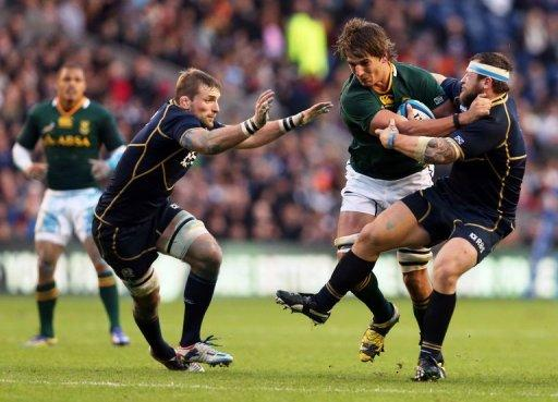Scotland's flanker John Barclay (L) and prop Ryan Grant (R) tackle South Africa's lock Eben Etzebeth (C)