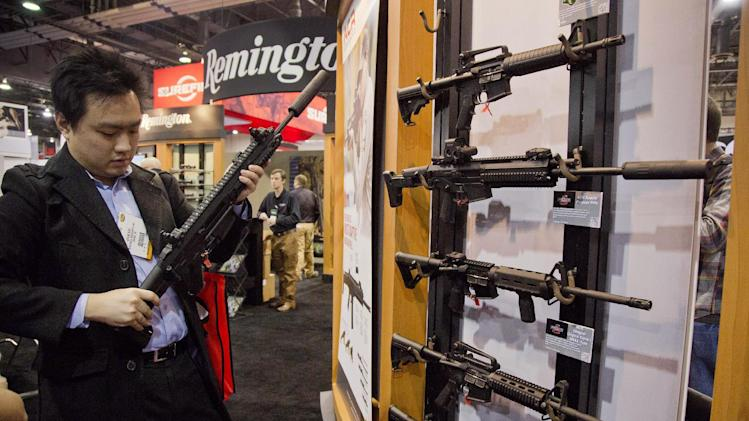 Accessories manufacturer Kevin Kao, of Irvine, Calif., examines a military grade Remington Adaptive Combat Rifle at the  35th annual SHOT Show, Tuesday, Jan. 15, 2013, in Las Vegas. The National Shooting Sports Foundation was focusing its 35th annual SHOT Show on products and services new to what it calls a $4.1 billion industry, with a nod to a raging national debate over assault weapons.  (AP Photo/Julie Jacobson)