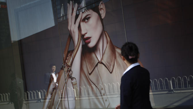 Chinese walks past a luxury advertising board in downtown Beijing, China, Friday, April 13, 2012.  China's economic growth fell to its lowest level in nearly three years in the first quarter but analysts said the economy should rebound in coming months. (AP Photo/ Vincent Thian)