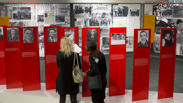Two women look at exhibits of the 'Berlin 1933 - the way to despotism' exhibition at the Topography of Terror museum in Berlin, Germany, Wednesday, Jan. 30, 2013. The Topography of Terror museum is located at the area where the headquarters of the Gestapo and SS were destroyed by allied bombing. (AP Photo/Michael Sohn)