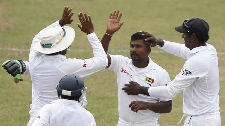 Sri Lanka's Herath celebrates with captain Mathews and teammates after taking the wicket of South Africa's de Kock during the fifth and final day of their second test cricket match in Colombo