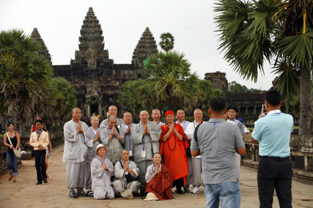 SIEM REAP, CAMBODIA - NOVEMBER 20: Korean tourists get their photo taken on the grounds of the Angkor Wat temple November 20, 2007 in Siem Reap, Cambodia. Tourism continues to grow to an average of 30 percent a year with new shopping centers and hotels lining the streets of Siem Reap. The Angkor Wat temple is a fast growing tourist destination with 1.7 million visiting last year. Preservationists in Cambodia, one of Southeast Asia&#39;s poorest countries, are seriously concern over damages created by constant overcrowding in touring the temple with numbers exceeding the capacity the site can manage. Angkor Wat was built between the ninth and fifteenth centuries, but was officially rediscovered in 1860 by French naturalist Henri Mouhot. The temple was later restored with the help of both UNESCO and archaeologists from France and Japan. (Photo Paula Bronstein/Getty Images)