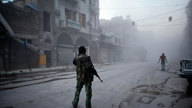 A rebel fighter stands on a street covered with dust following a reported air strike by Syrian government forces in the old city of Aleppo on July 21, 2014