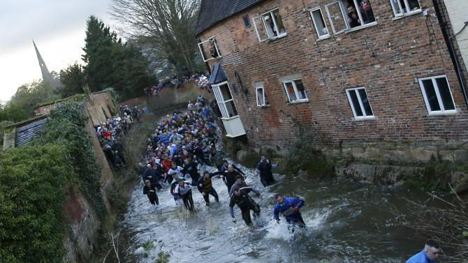 A player breaks with the ball during the annual Shrovetide football match in Ashbourne