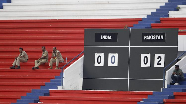 Indian policemen sit next to the scoreboard in empty stands as they watch members of Pakistan team celebrate their win during the last match of the two-match friendly soccer tournament between India and Pakistan in Bangalore, India, Wednesday, Aug. 20, 2014. Pakistan won the match 2-0 to level the series. (AP Photo/Aijaz Rahi)