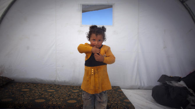In this Wdnesday, Nov. 7, 2012 photo, Fatma Zatar, 2, who fled with her family from the violence in their village poses for a portrait inside a tent at a camp in the village of Atmeh, near the Turkish border with Syria. Most of the displaced people in the tent camp rising near this village on the Syrian-Turkish border are children. All have fled the violence of Syria's civil war further south. Many have seen violence themselves, some have lost relatives, and most have trouble sleeping and panic when they hear loud noises or airplanes, their parents say. The Atmeh camp was born of necessity about three months ago, say the local rebels who run the place, distributing tents and food aid provided by a smattering of aid organizations.(AP Photo/Khalil Hamra)