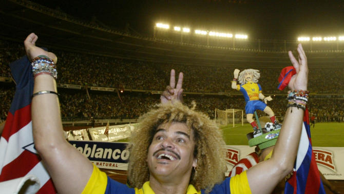 """FILE- In this Feb. 1, 2004, file photo, Carlos """"El Pibe"""" Valderrama waves at the end of an exhibition game to formalize his retirement from professional soccer in the coastal city of Baranquilla, in northern Colombia. """"El Pibe"""" lived up to his candid nature by declaring that the teams he captained in the 1990's would have advanced further in World Cup play had the players been freed from chastity. (AP Photo/Ricardo Mazalan, File)"""