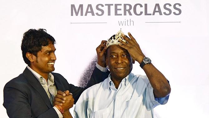 Legendary Brazilian soccer player Pele adjusts a crown made of gold and silver presented to him by a fan at a promotional event in Kolkata