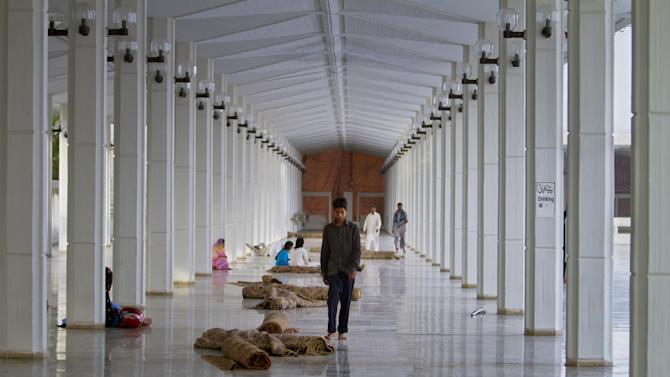 A Pakistani boy walks on the corridor looking for a good place to rest after offering his afternoon prayers at Grand Faisal mosque during Ramadan in Islamabad, Pakistan, Monday, July 6, 2015. Muslims across the world are observing the holy fasting month of Ramadan, where they refrain from eating, drinking and smoking from dawn to dusk. (AP Photo/Anjum Naveed)