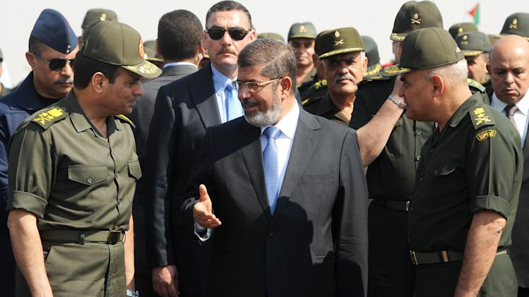FILE - In this Wednesday, Oct. 10, 2012 file photo released by the Egyptian Presidency, then Egyptian President Mohammed Morsi, center, speaks with Minister of Defense, Lt. Gen. Abdel-Fattah el-Sissi, left, at a military base in Ismailia, Egypt. An Egyptian court has set Nov. 4, 2013, as the start date for the trial of ousted President Mohammed Morsi on charges of incitement to murder for the killings of opponents who were rallying outside his palace while he was in office. Morsi, ousted in a popularly-backed military coup in July, has been held incommunicado since. (AP Photo/Egyptian Presidency)