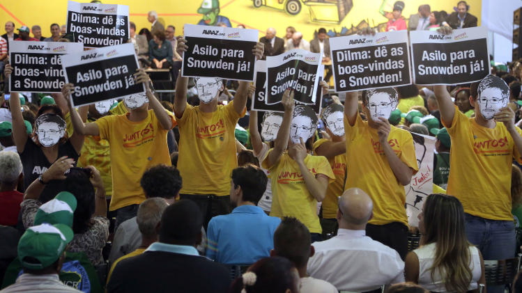 "Demonstrators wearing masks depicting National Security Agency leaker Edward Snowden and holding posters that reads in Portuguese; ""Dilma, give a welcome to Snowden,"" and ""Asylum for Snowden now,""crash a Christmas ceremony while Brazil's President Dilma Rousseff delivers a speech to recycling workers and homeless people, in Sao Paulo, Brazil, Thursday, Dec. 19, 2013. News accounts in Brazil based on documents leaked by Snowden detailed how the NSA monitored the cellphone of the Brazilian leader. She responded by canceling a planned state visit to the U.S. (AP Photo/Andre Penner)"