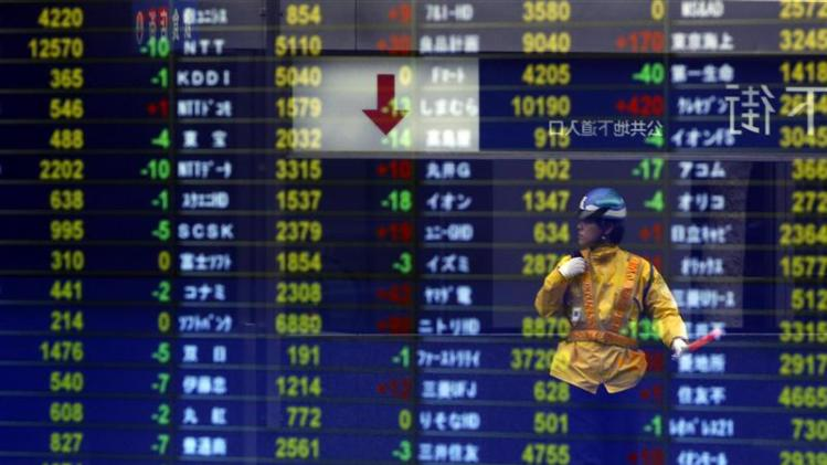 A traffic controller at a constructing site is reflected on a stock quotation board at a brokerage in Tokyo
