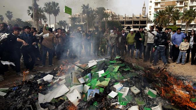 """FILE - In this Wednesday, March 2 , 2011 file photo, Libyan protesters burn copies of Libyan leader Moammar Gadhafi's """"Green Book"""" during a demonstration against him in Benghazi, eastern Libya.  A new law that excludes former officials of the Moammar Gadhafi era from public office is dividing Libya and deepening the turmoil that has plagued the country since the civil war that ousted the erratic leader. Passed by lawmakers essentially at gunpoint, it bans not just those who held office but even clerics who glorified the dictator and researchers who worked on his notorious political tract, the Green Book. (AP Photo/Kevin Frayer, File)"""