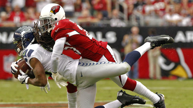 Seattle Seahawks wide receiver Sidney Rice makes the catch as Arizona Cardinals cornerback Patrick Peterson makes the tackle during the first half of an NFL football game, Sunday, Sept. 9, 2012, in Glendale, Ariz. (AP Photo/Matt York)