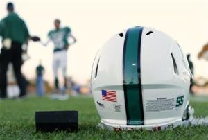 A football helmet's health warning sticker is pictured between a U.S. flag and the number 55, in memory of former student and NFL player Junior Seau, as the Oceanside Pirates high school football team prepares for their Friday night game in Oceanside