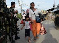 Residents affected by the standoff between Muslim gunmen and army troops walk past soldiers as they evacuate to a safer area in Zamboanga City, on the southern island of Mindanao on September 10, 2013. (AFP Photo/Ted Aljibe)