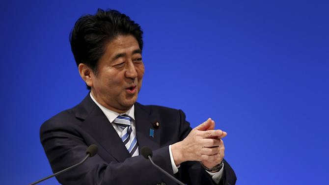 Japan's PM Abe, who is also the ruling Liberal Democratic Party (LDP) leader, mimics a gesture done frequently by Japan's rugby player Ayumu Goromaru, as he delivers a speech during a ceremony for the LPD's 60th anniversary in Tokyo
