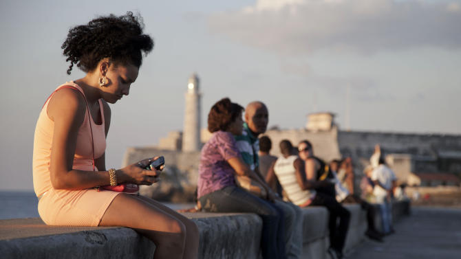 """In this March 11, 2014 photo, a woman uses her cellphone as she sits on the Malecon in Havana, Cuba. The U.S. Agency for International Development masterminded the creation of a """"Cuban Twitter,"""" a communications network designed to undermine the communist government in Cuba, built with secret shell companies and financed through foreign banks, The Associated Press has learned. The project, which lasted more than two years and drew tens of thousands of subscribers, sought to evade Cuba's stranglehold on the Internet with a primitive social media platform. (AP Photo/Franklin Reyes)"""