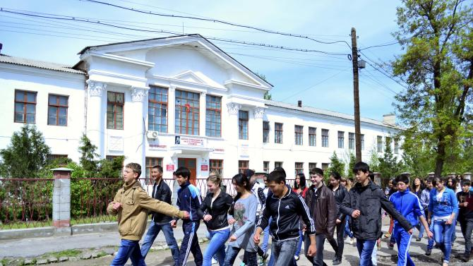 Schoolchildren march in front of a school where Tamerlan Tsarnaev, who was dubbed a suspect in the Boston Marathon bombings, studied, in a small Kyrgyz city Tokmok east of the country's capital of Bishkek, on Friday, April 20, 2013. Tamerlan Tsarnaev was an amateur boxer with muscular arms and enough brio to arrive at a sparring session without protective gear. The Tsarnaev family arrived in the United States, seeking refuge from strife in their homeland. The family had moved from Kyrgyzstan to Dagestan, a predominantly Muslim republic in Russia's North Caucasus that has become an epicenter of the Islamic insurgency that spilled over from Chechnya. (AP Photo/Abylay Saralayev)