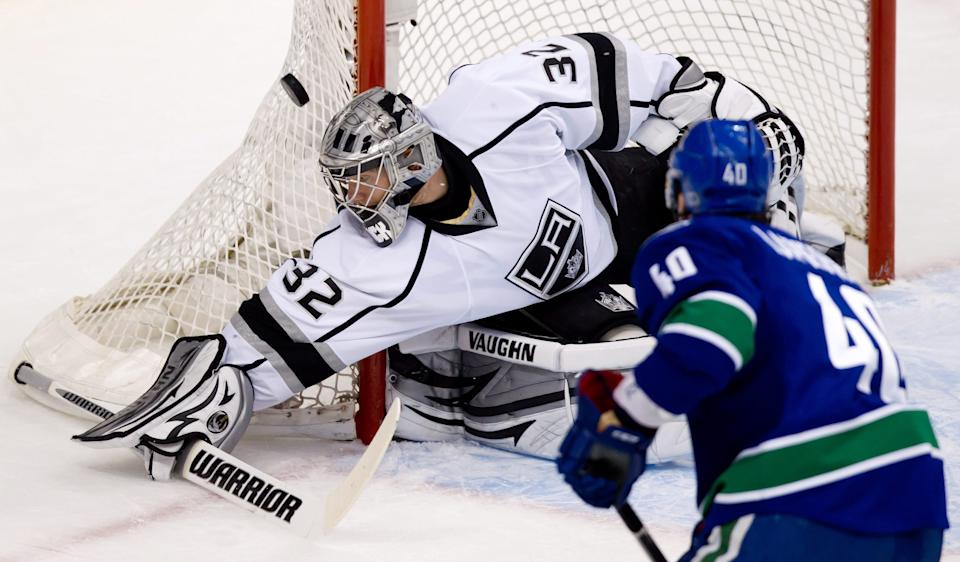 Los Angeles Kings goalie Jonathan Quick, left, deflects Vancouver Canucks' Maxim Lapierre's shot wide of the goal during the first period of Game 5 of an NHL Western Conference quarterfinal Stanley Cup playoff hockey series in Vancouver, B.C., on Sunday, April 22, 2012. (AP Photo/The Canadian Press, Darryl Dyck)