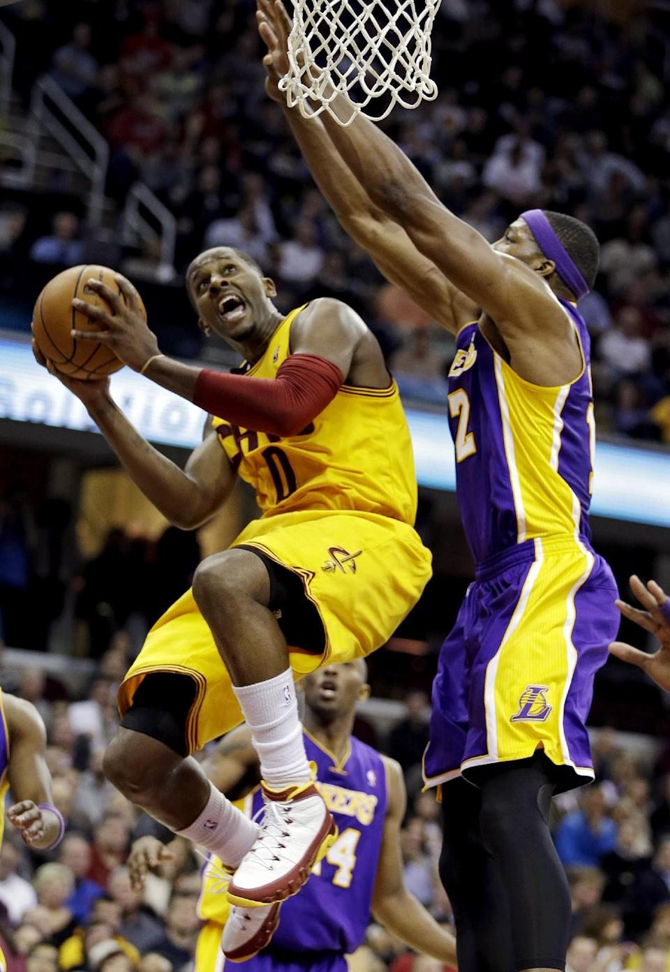 Cleveland Cavaliers' C.J. Miles, left, goes in for a shot against Los Angeles Lakers' Dwight Howard in the second quarter of an NBA basketball game, Tuesday, Dec. 11, 2012, in Cleveland. (AP Photo/Mark Duncan)
