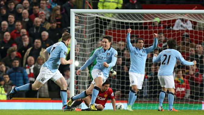 Manchester City's James Milner, left, celebrates with Samir Nasri, 2nd left, after scoring the opening goal during the English Premier League soccer match against Manchester United at Old Trafford Stadium, Manchester, England, Monday April 8, 2013. (AP Photo/Jon Super)