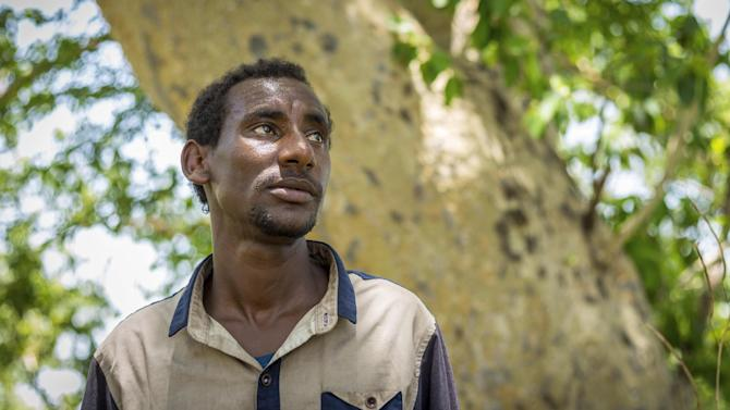 In this photo taken Thursday, June 4, 2015, Getachew Merah, a 30-year-old migrant from Ethiopia, stands by a tree near Metema, in northwestern Ethiopia next to the border with Sudan. The town is a center for a booming trade in migrants from Ethiopia, Eritrea, Somalia and Sudan, with many hoping to make their way to Europe, but life here is now a cat-and-mouse game: The authorities are cracking down, yet the migrants just keep coming, often risking death. (AP Photo/Mulugeta Ayene)