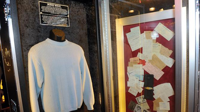 """A sweater worn by Buddy Holly during his 1958 tour of England along with Tommy Allsup's wallet, right, which was recovered from the wreckage of the Buddy Holly plane crash, are on display at Hard Rock International's traveling music memorabilia tour, """"Gone Too Soon,"""" at Hard Rock Cafe New York, Wednesday, Feb. 13, 2013. """"Gone Too Soon"""" pays tribute to music icons whose lives and career where tragically cut short and will be on tour at Hard Rock locations in the U.S. throughout 2013. (Photo by Diane Bondareff/Invision for Hard Rock International/AP Images)"""