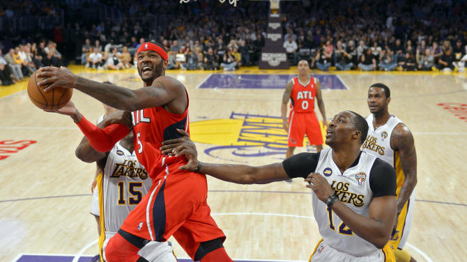 Atlanta Hawks forward Josh Smith, center, goes up for a shot as Los Angeles Lakers forward Metta World Peace, left, and center Dwight Howard defend during the first half of their NBA basketball game, Sunday, March 3, 2013, in Los Angeles. (AP Photo/Mark J. Terrill)