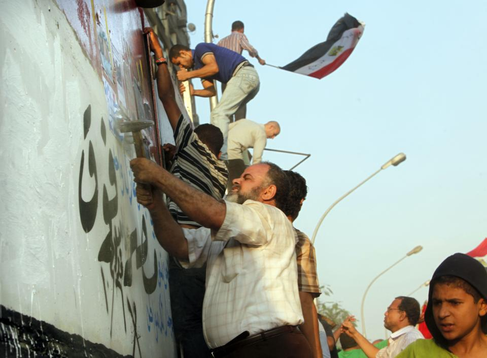 "Egyptian activists demolish a concrete wall built around a building housing the Israeli embassy in Cairo, Egypt, to protect it against demonstrators, as they raise their national Friday, Sept.9, 2011. Arabic writing reads "" Egypt is over all"". (AP Photo/Amr Nabil)"