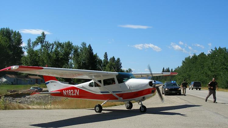 In this photo released on Thur. July 21,2011 by the Montana Highway Patrol showing the plane of a retired air traffic controller who's engine died and was forced to make an emergency landing of his Cessna 182 on U.S. Highway 93 just north of Darby onThur., July 21,2011. (AP Photo/Montana Highway Patrol,Scott Bennett)